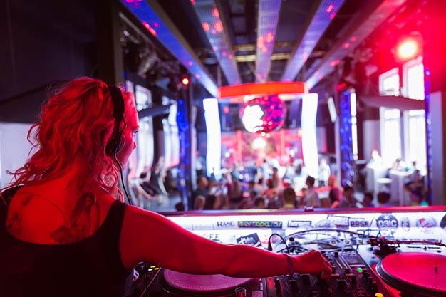 DJane Anne Decks hinter ihrem Controller mit Blick auf das tanzende Publikum